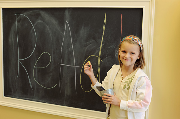 Young girl at chalkboard